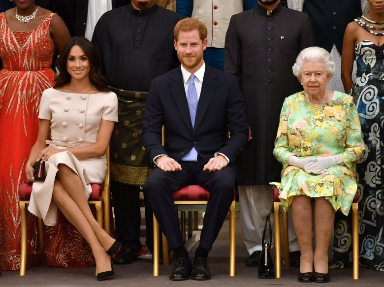 Queen Elizabeth, Prince Harry and Meghan, the Duchess of Sussex, pose for a picture at a Buckingham Palace reception following the final Queen's Young Leaders Awards ceremony in London on June 26, 2018. Both Meghan and Harry spoke warmly of the Queen during the interview Sunday night.(John Stillwell/Reuters)