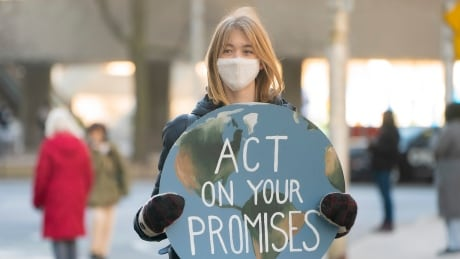 A youth climate protester with a decorated sign