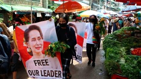 Anti-coup protesters walk through Yangon market