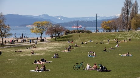 People are pictured in the sun on Sunset Beach in Vancouver, B.C., on Friday, April 16, 2021. (Ben Nelms/CBC)