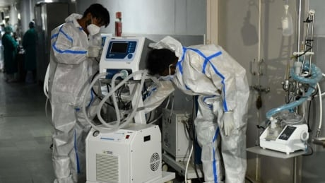 Health workers place a ventilator machine in hallway of a hospital in Amritsar, India