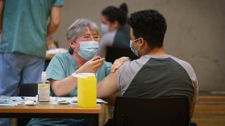 A vaccinator inoculates Montreal high school student