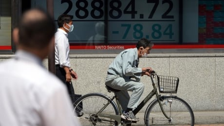 Masked man rides bicycle past board showing Nikkei readouts