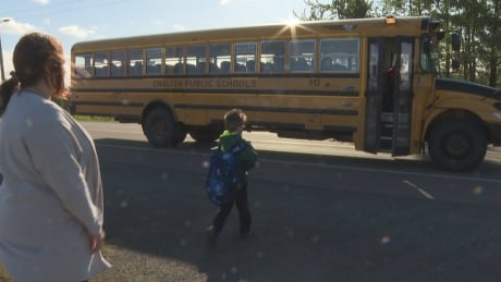 Little boy Harlan gets on school bus in Cardigan, P.E.I., as his mom Mandy Acorn watches