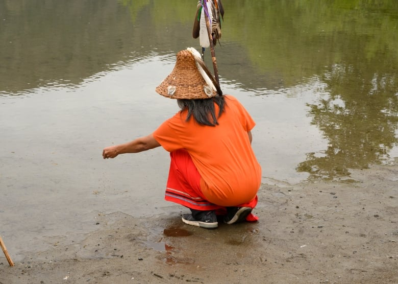 a child sprinkling tobacco on the river water