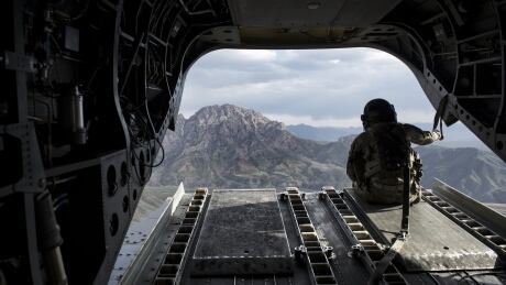 U.S. soldier looks out from a helicopter flying above Afghanistan's Logar province