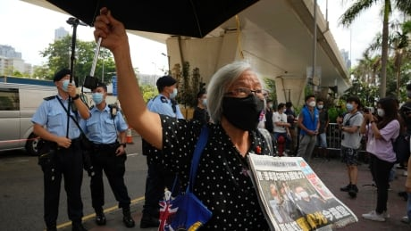 Pro-democracy activist holds copy of Apple Daily paper outside Hong Kong court
