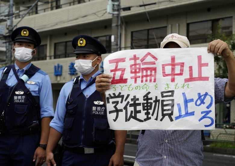 anti olympics protester holds sign next to police officers in tokyo