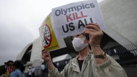 A protester holds an anti-Olympics sign near Tokyo's Komazawa Olympic Park