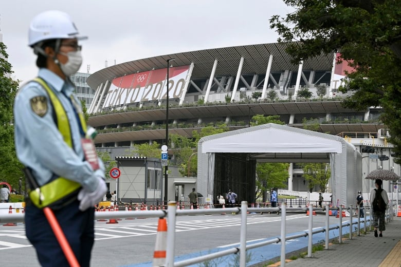masked security guard standing outside tokyo s national stadium