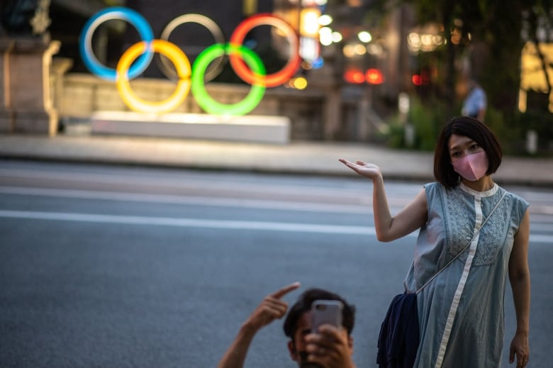 couple poses in front of a sign displaying the olympic rings image in tokyo