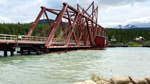 Crews face 'constant battle' with flood waters touching bottom of Carcross train bridge