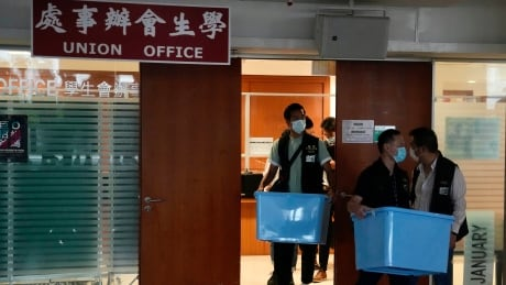 Hong Kong police carry documents from office of student union