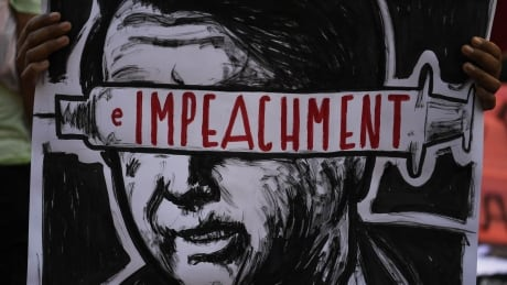 Protester holding placard with illustration of Brazilian president Jair Bolsonaro on it