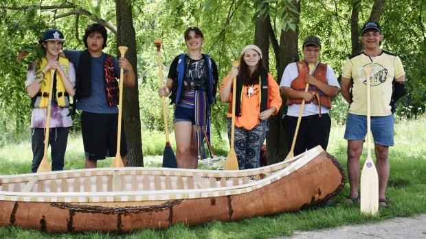 Indigenous students paddle handmade birch bark canoe on Speed River