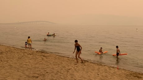Children play on the Hot Sands Beach near the Okanagan Lake with low visibility of William R. Bennett Bridge amid heavy wildfire smoke on July 30, 2021.