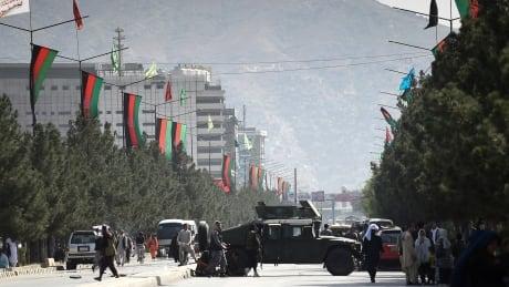 Taliban fighters block a road near Kabul airport