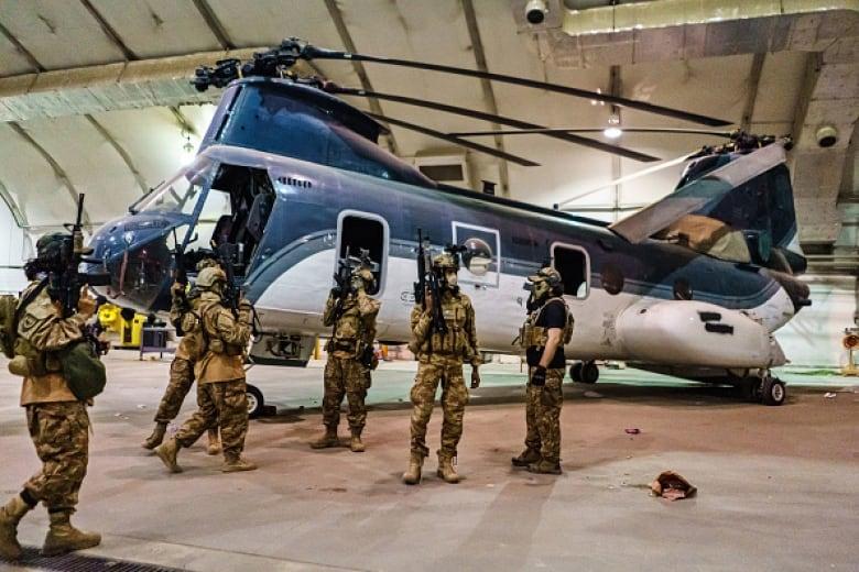 оевики Талибана осматривают оборудование, оставшееся после того, как военные США завершили вывод войск в аэропорту Кабула во вторник. (Маркус Ям / Los Angeles Times / Getty Images)