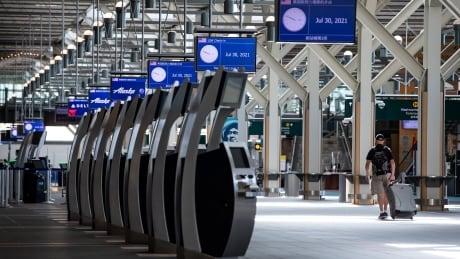 Traveller pulling baggage through U.S. departures check-in area at Vancouver airport