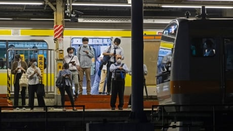 Commuters wear face masks as they await a train at a station in Tokyo