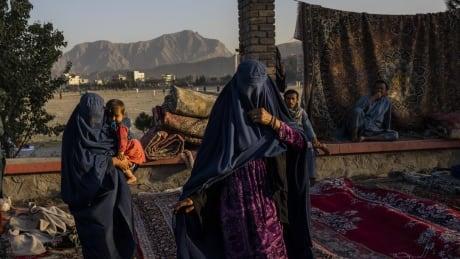 Afghan women walk through a Kabul market