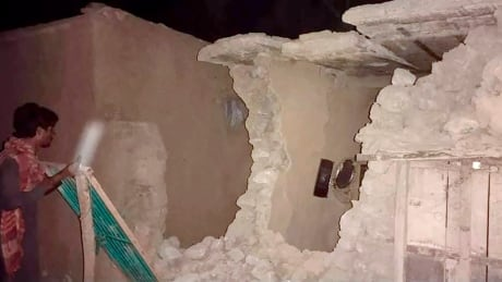 Man inspects damaged home in wake of earthquake in southwestern Pakistan
