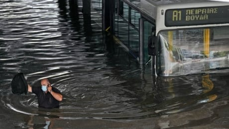 Greek bus driver holds mobile phone while wading through high water in Athens
