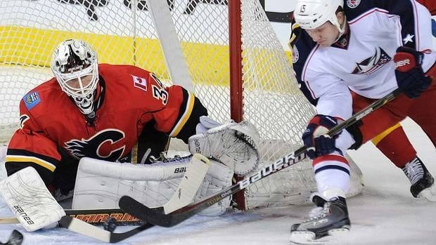 Chicago Blackhawks' Andrew Shaw, right, swats the puck past Calgary Flames goalie Miikka Kiprusoff on Saturday.